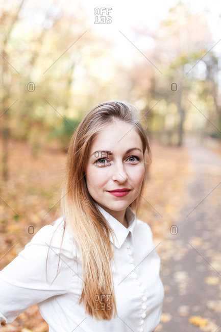 The woman is walking at the sunny park in autumn and is smiling