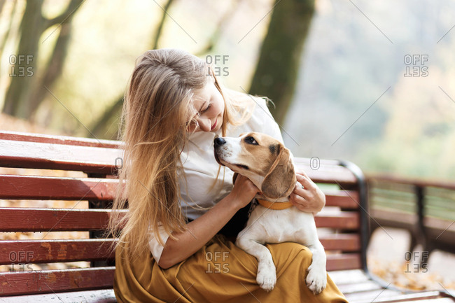 The woman teaches the beagle puppy commands while at the park and hugging