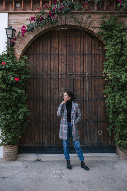 Young woman with plaid coat walking in the city