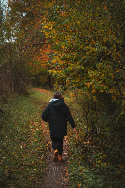 Girl on a black jacket walking through the trail on an autumnal landscape
