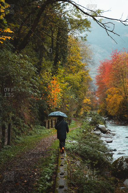 Girl on a black jacket walking by the river under an umbrella on an autumnal landscape