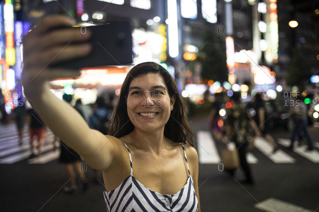 Young woman taking a selfie at night in the streets of Shinjuku- Tokyo- Japan