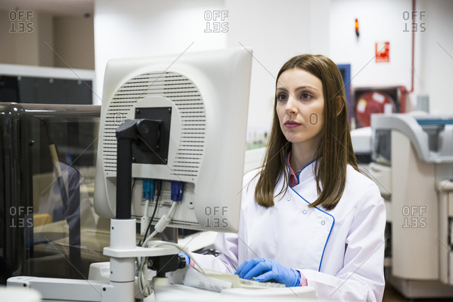 Young woman in white apparel using sample analyzer while working in research laboratory