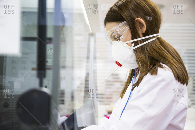 Young woman wearing safety mask and goggles while working in a laboratory