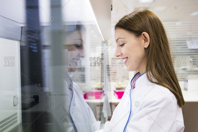 Side view of female scientist in white apparel working in modern laboratory
