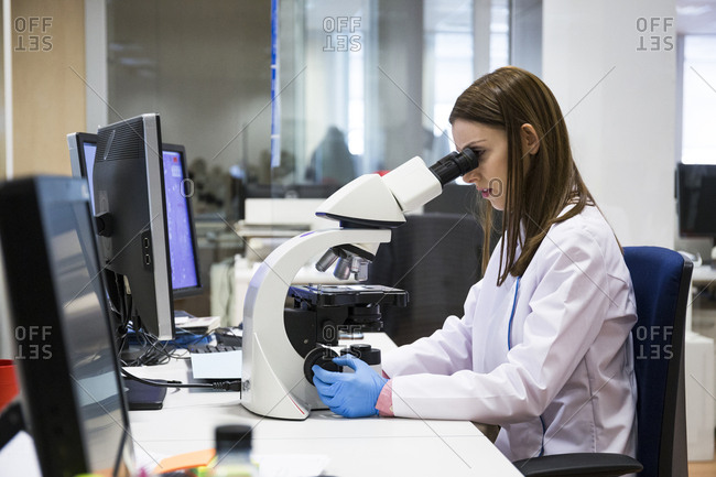 Young woman examining samples with microscope while working in modern laboratory