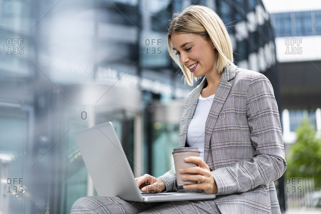Smiling young businesswoman using laptop in the city
