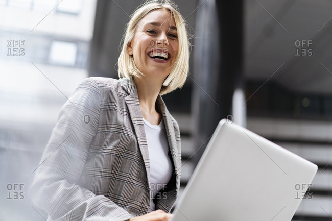 Portrait of happy young businesswoman with laptop in the city