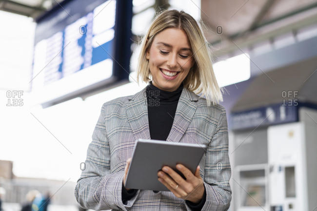 Smiling young businesswoman using tablet at the train station
