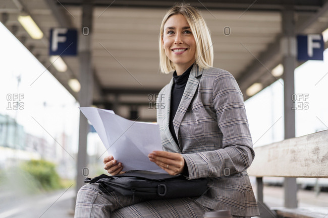 Smiling young businesswoman with papers at the train station
