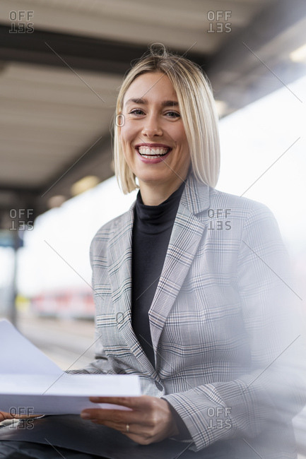 Portrait of happy young businesswoman with papers at the train station