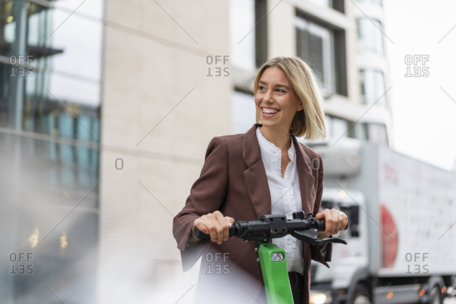 Happy young businesswoman with e-scooter in the city