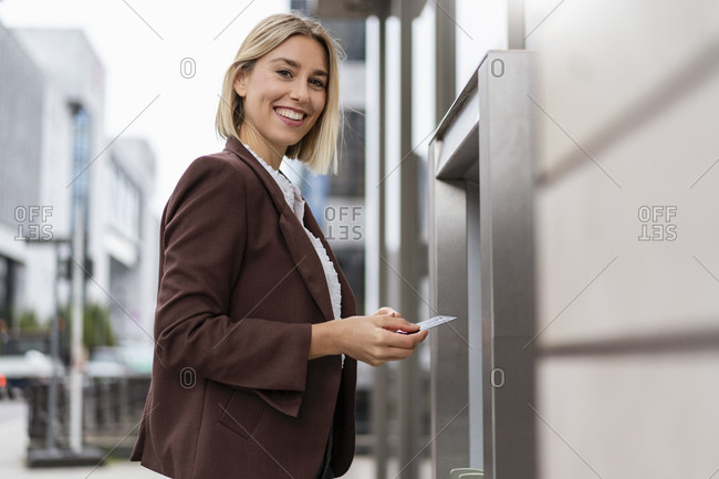 Portrait of smiling young businesswoman withdrawing money at an ATM in the city
