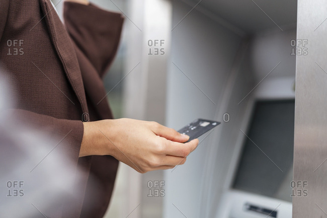 Close-up of businesswoman withdrawing money at an ATM