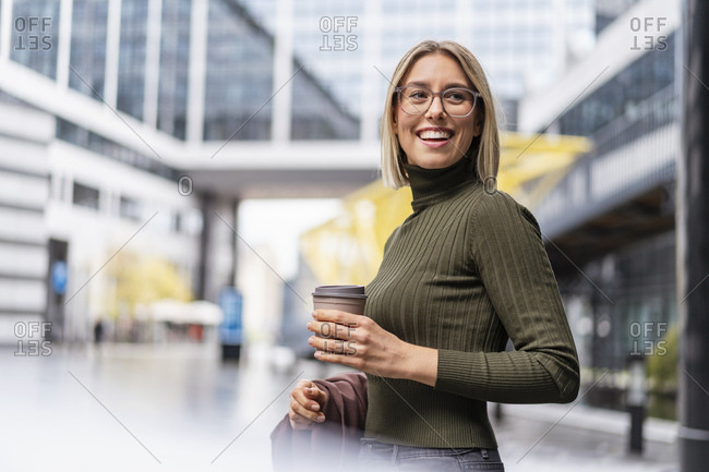 Happy young woman with takeaway coffee in the city