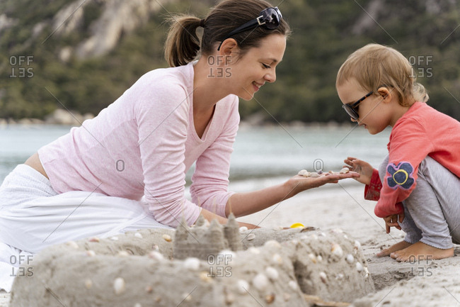 Happy mother and daughter building a sand castle on the beach