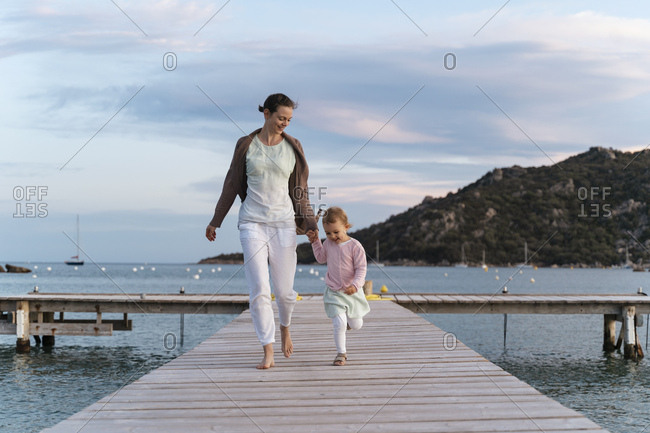 Happy mother with daughter walking on a jetty at sunset