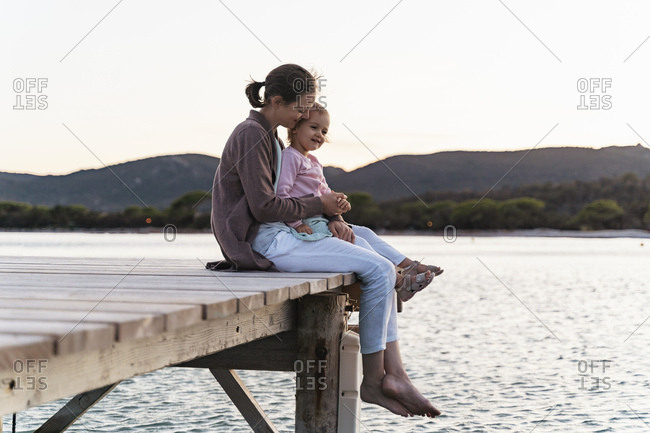 Happy mother with daughter sitting on a jetty at sunset
