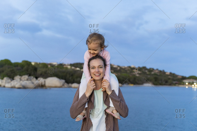 Portrait of mother carrying her daughter on shoulders at the seafront at sunset