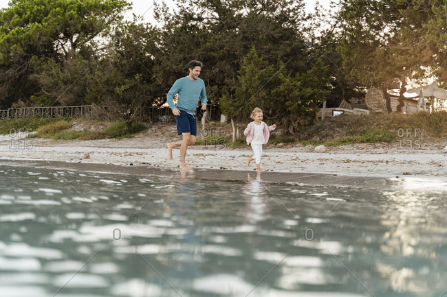 Happy father running with daughter on the seashore