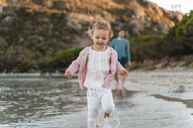 Happy girl running on the seashore with father in background