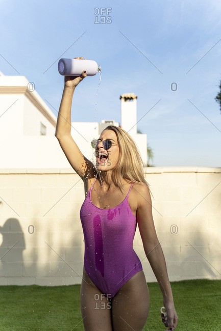 Portrait of screaming woman wearing sunglasses and pink swimsuit   pouring water from bottle on herself