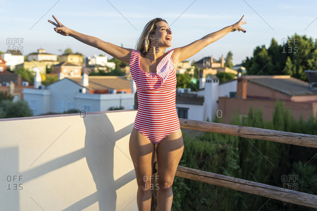 Portrait of happy woman standing on roof terrace showing victory sign- Sevilla- Spain