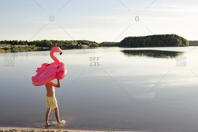 Young man with flamingo pool float walking at lakeshore