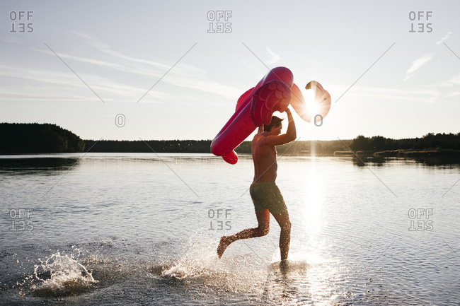 Young man running with flamingo pool float into a lake