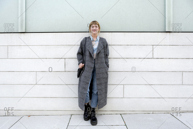 Portrait of strawberry blonde young woman wearing grey coat leaning against wall