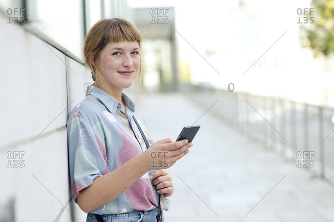 Portrait of strawberry blonde young woman with cell phone