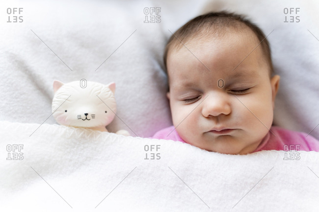 Portrait of sleeping baby girl with cat toy