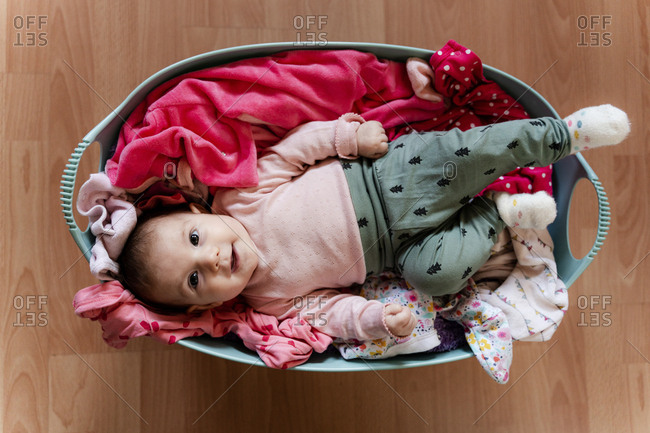Baby girl in the laundry basket with clothes to clean