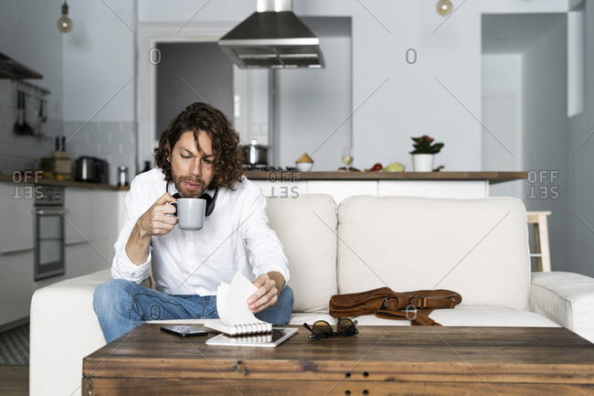 Man sitting on couch at home with coffee mug and notepad
