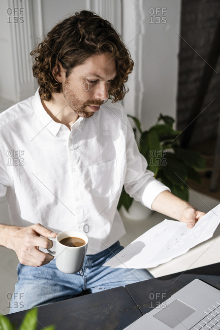 Man sitting at table at home reviewing papers