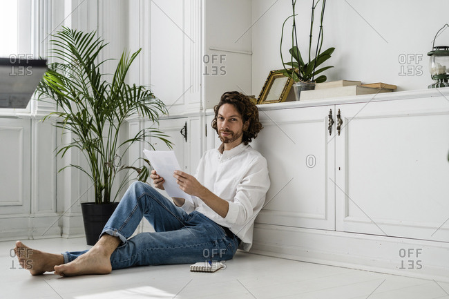 Portrait of man sitting on the floor at home reviewing papers