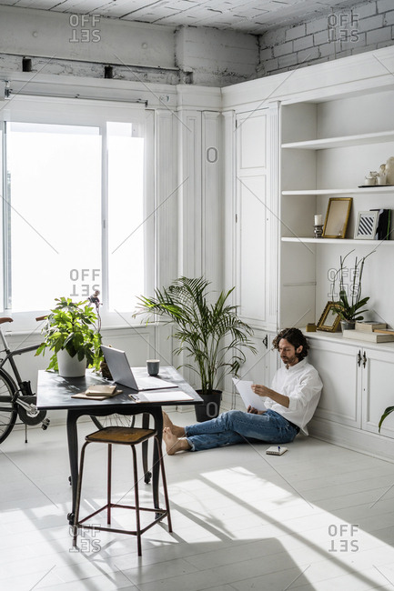 Man sitting on the floor at home reviewing papers