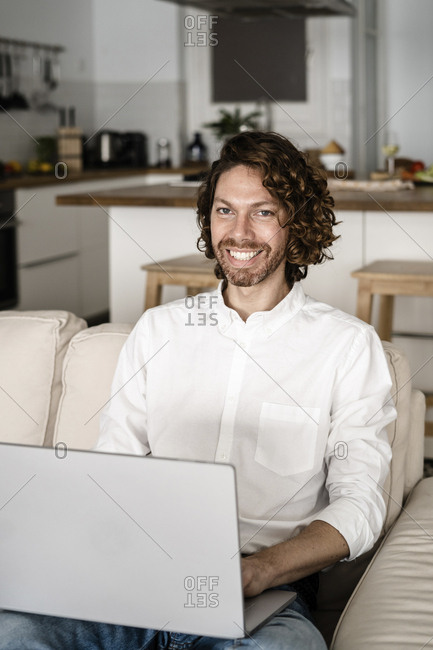Portrait of smiling man using laptop on couch at home