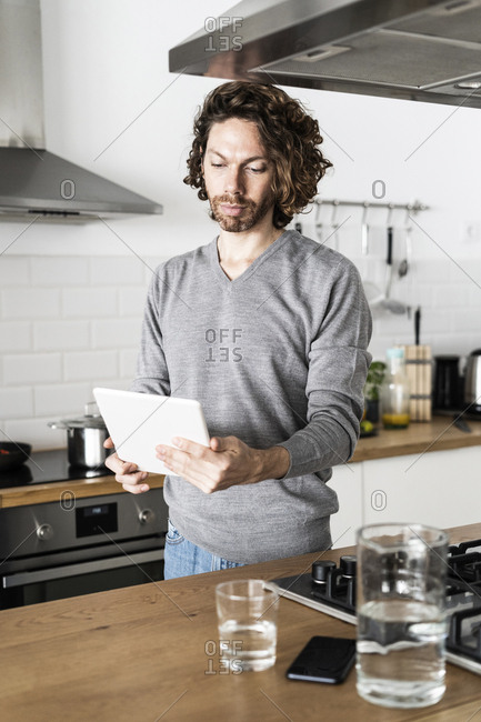 Man using tablet in kitchen at home