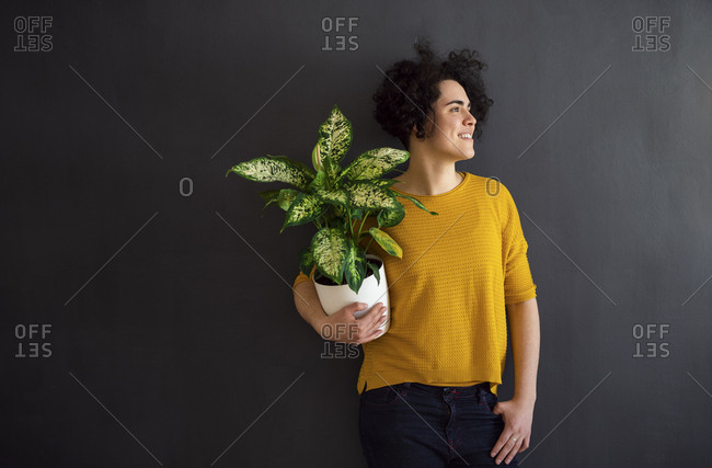 Portrait of young woman holding a house plant and looking sideways
