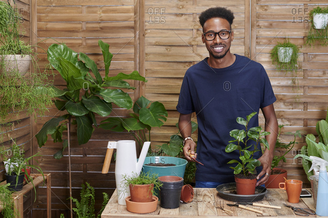 Portrait of a smiling young man repotting a plant on his terrace