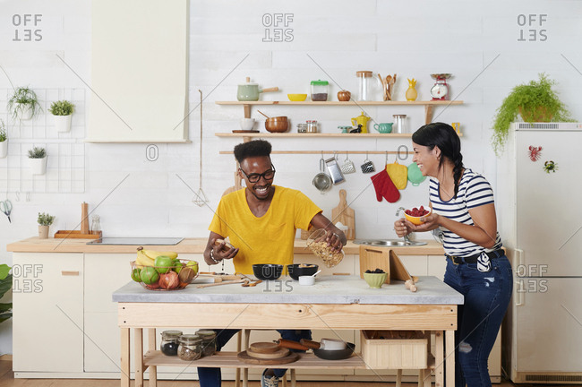 Multiethnic couple laughing- breakfasting together in the kitchen