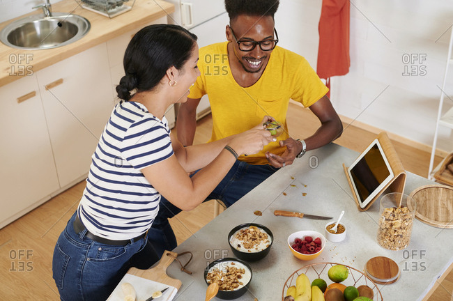 Multiethnic couple breakfasting together in the kitchen- talbet in holder