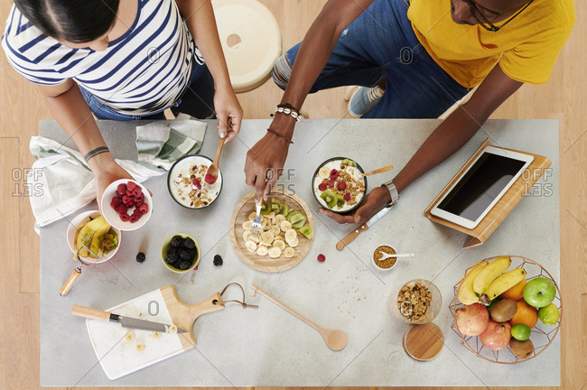 Multiethnic couple breakfasting together in the kitchen- from above