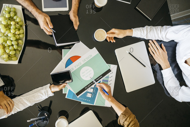 Close-up of coworkers working together on table