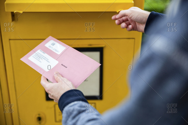 Elector holding documents for the postal vote in front of the mailbox