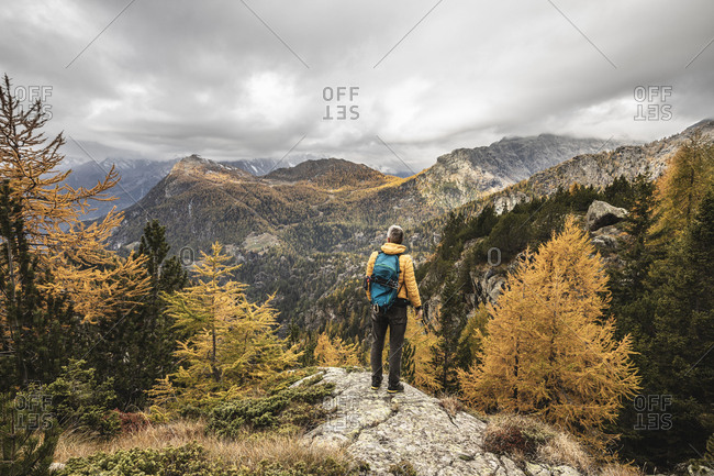 Hiker standing and looking over alpine plateau in autumn- Sondrio- Italy