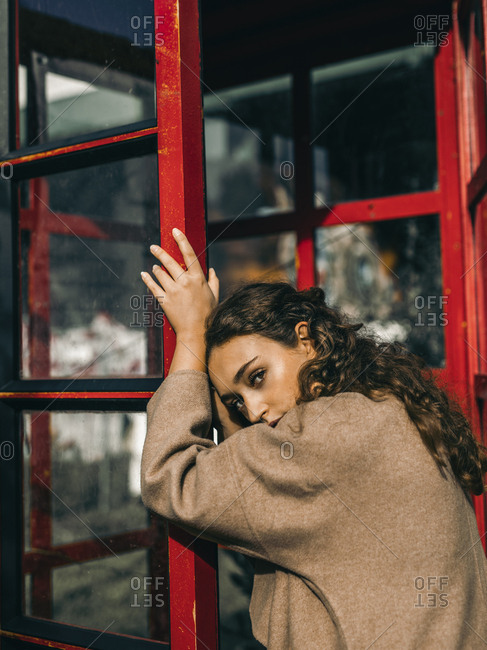 Young woman leaning on a telephone box