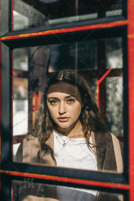 Young woman in a telephone box- looking at camera