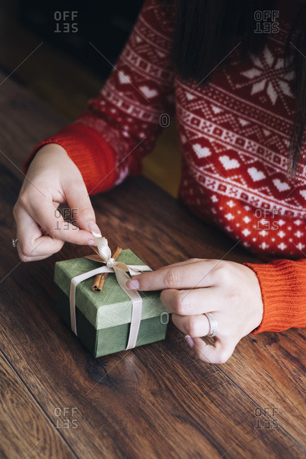 Woman's hands decorating Christmas present